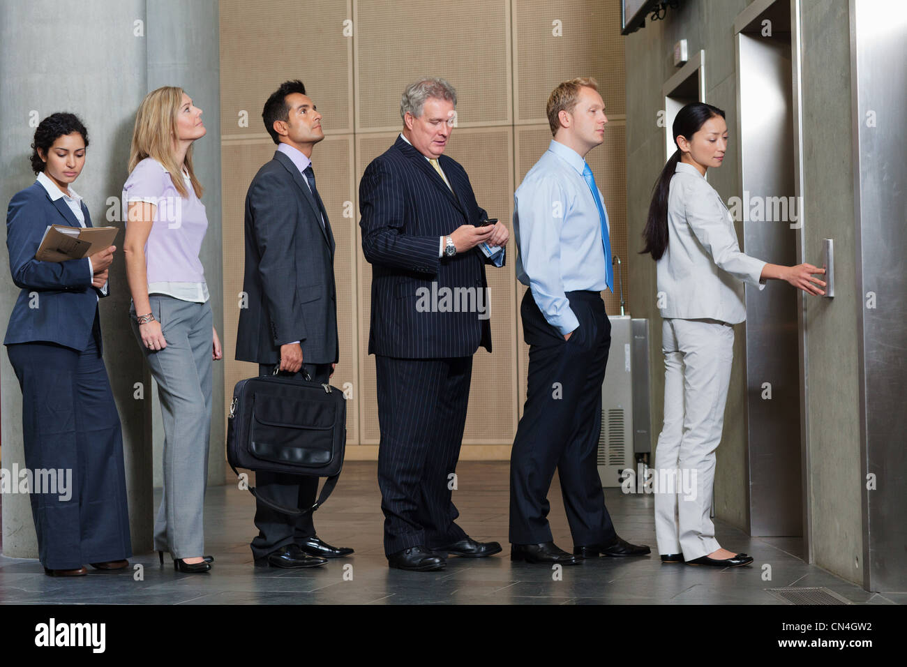 Businesspeople waiting in queue for elevator - Stock Image