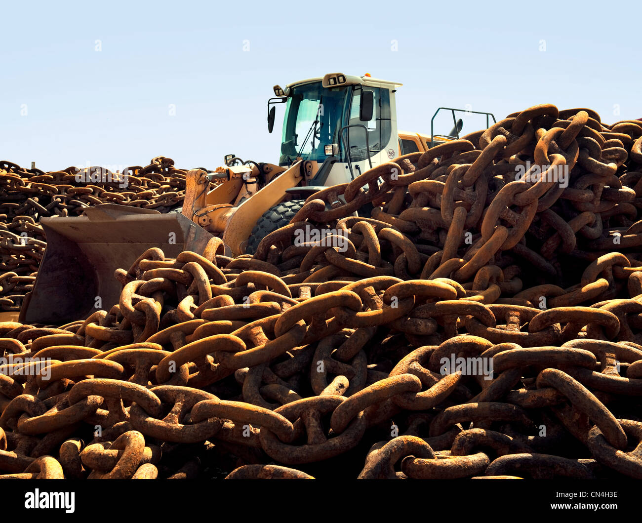 Rusted chains and excavator in scrap yard - Stock Image