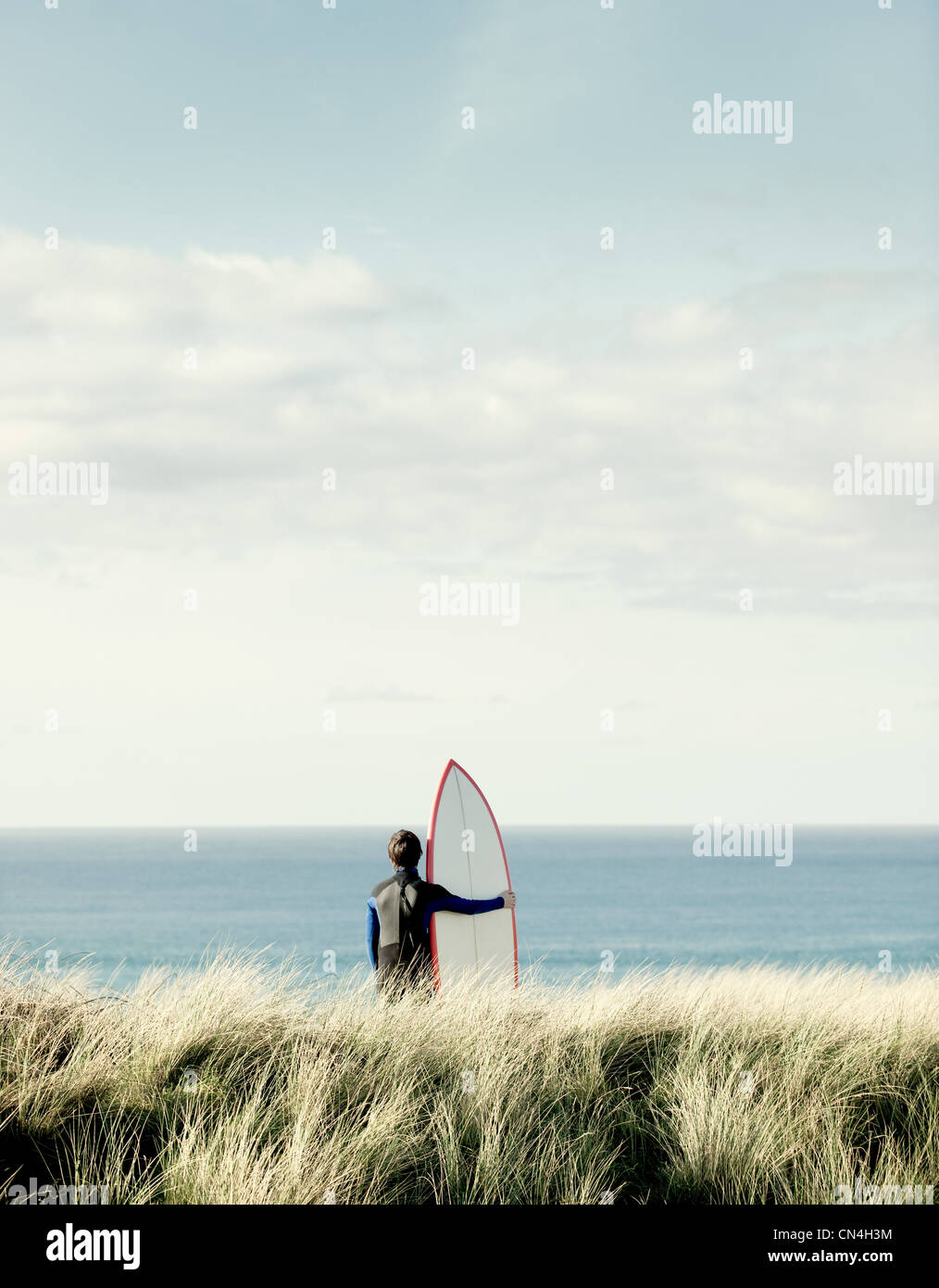 Surfer looking out to sea - Stock Image