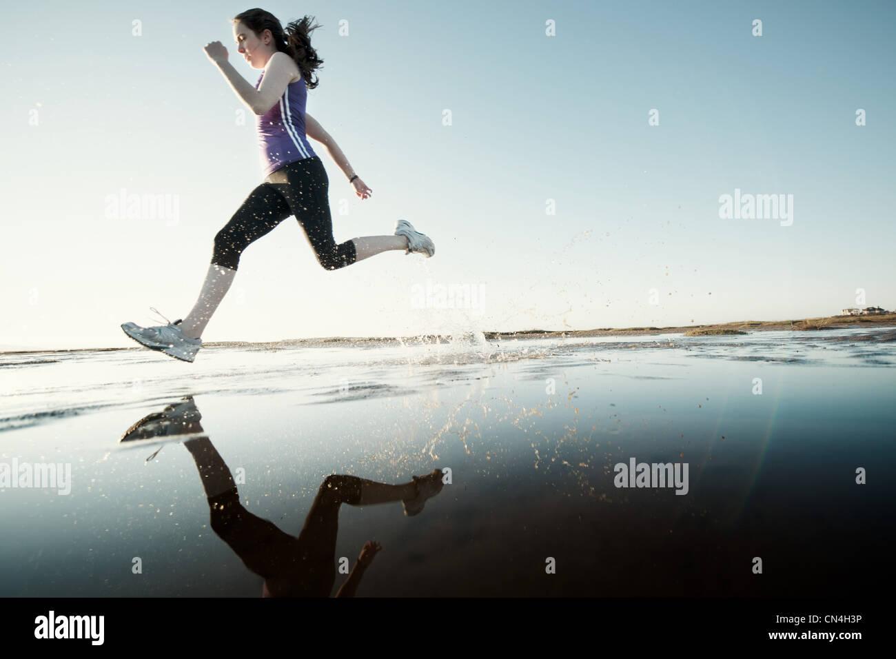 Teenage girl running on water - Stock Image