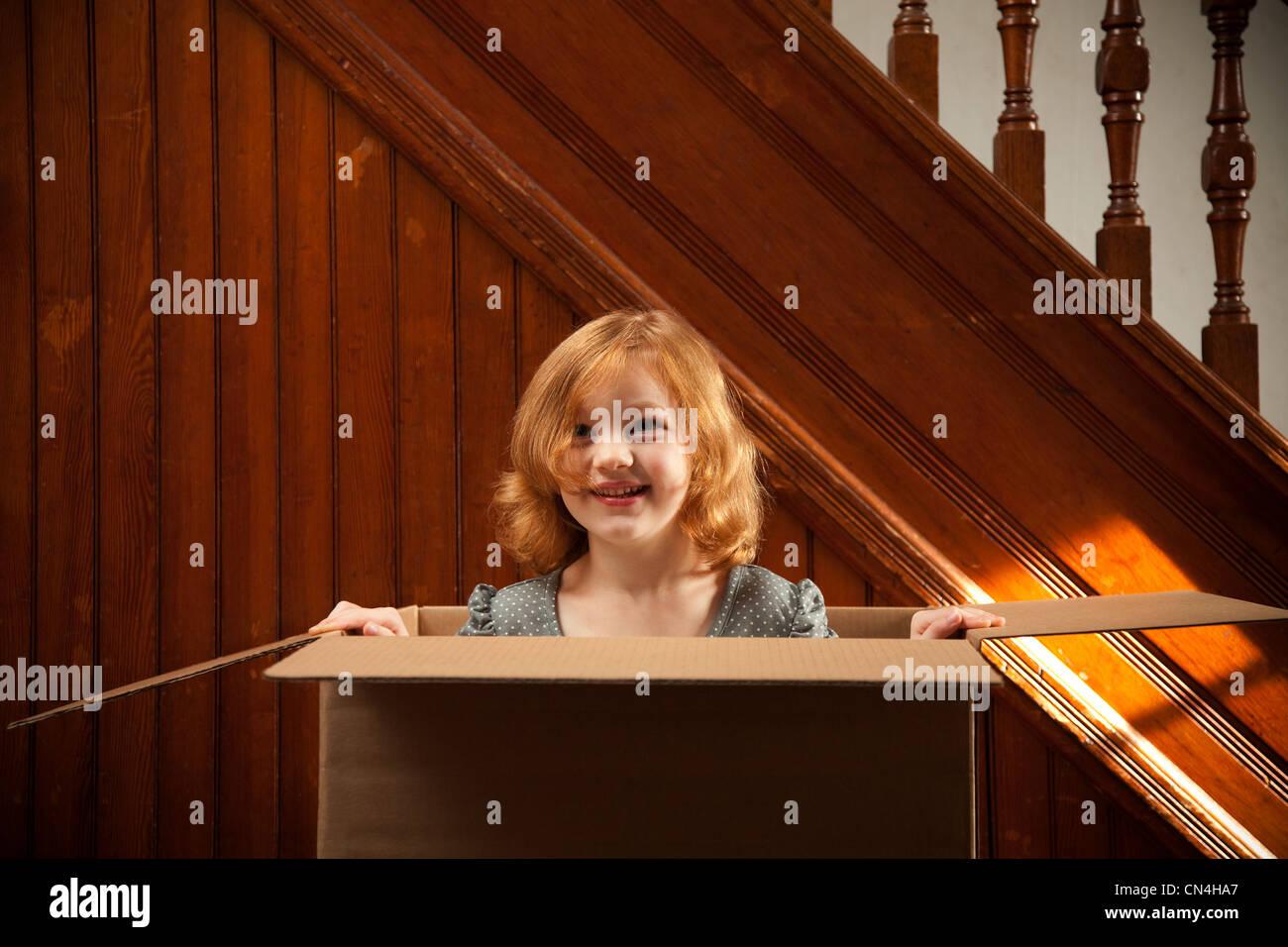 Portrait of girl hiding in cardboard box - Stock Image