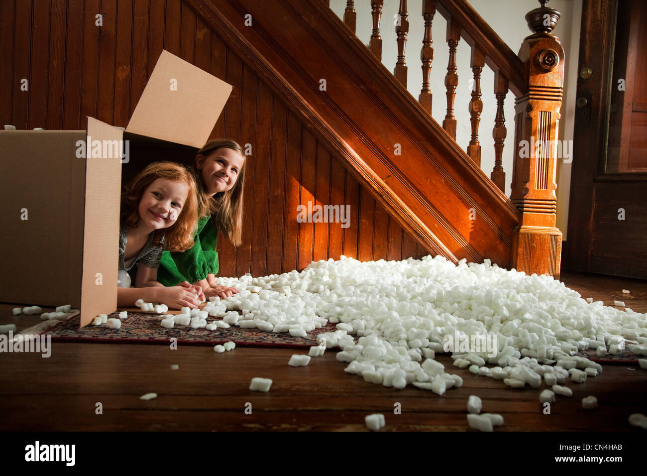 Portrait of girls hiding in cardboard box - Stock Image