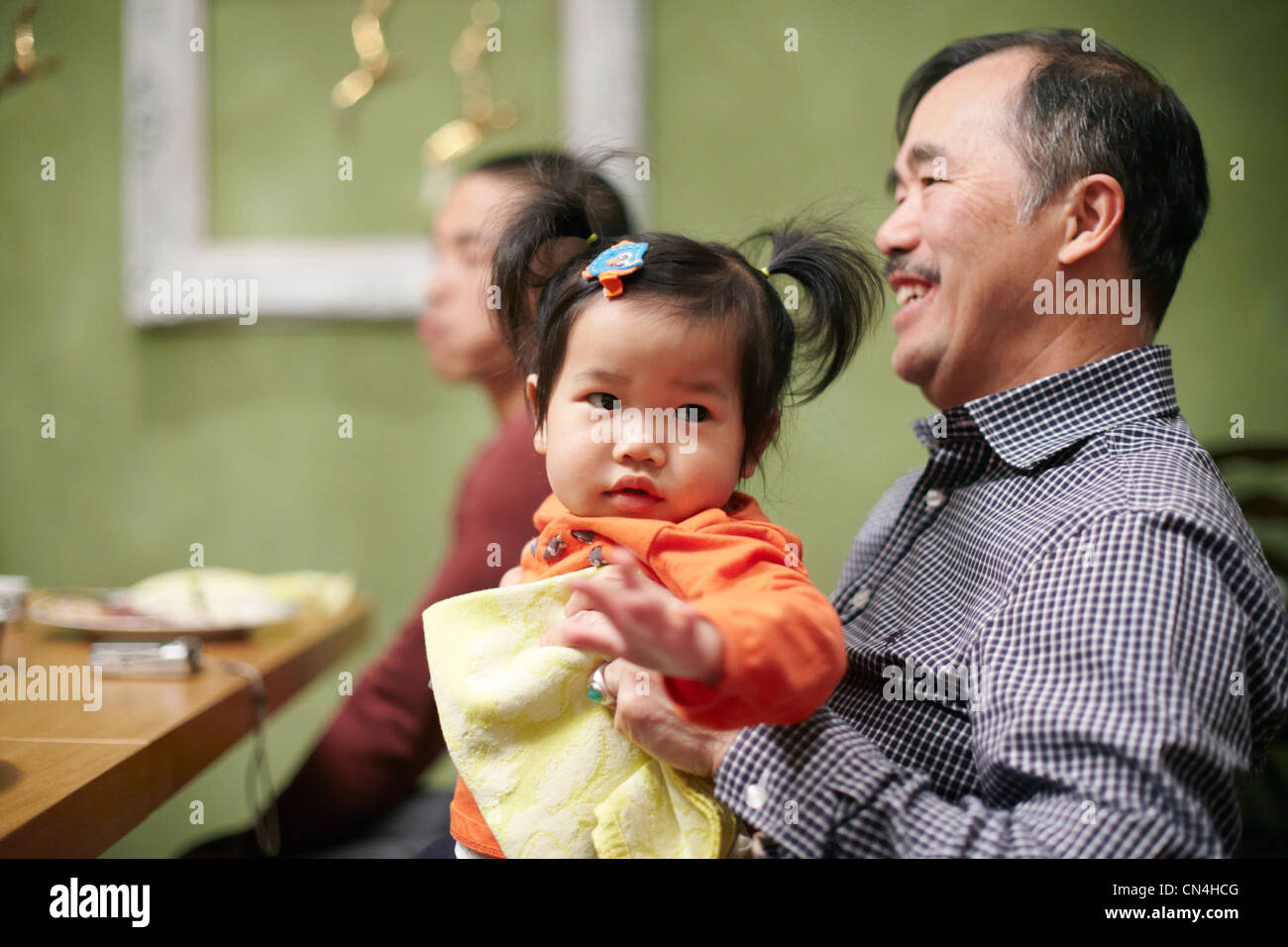 Toddler and grandfather at thanksgiving dinner - Stock Image