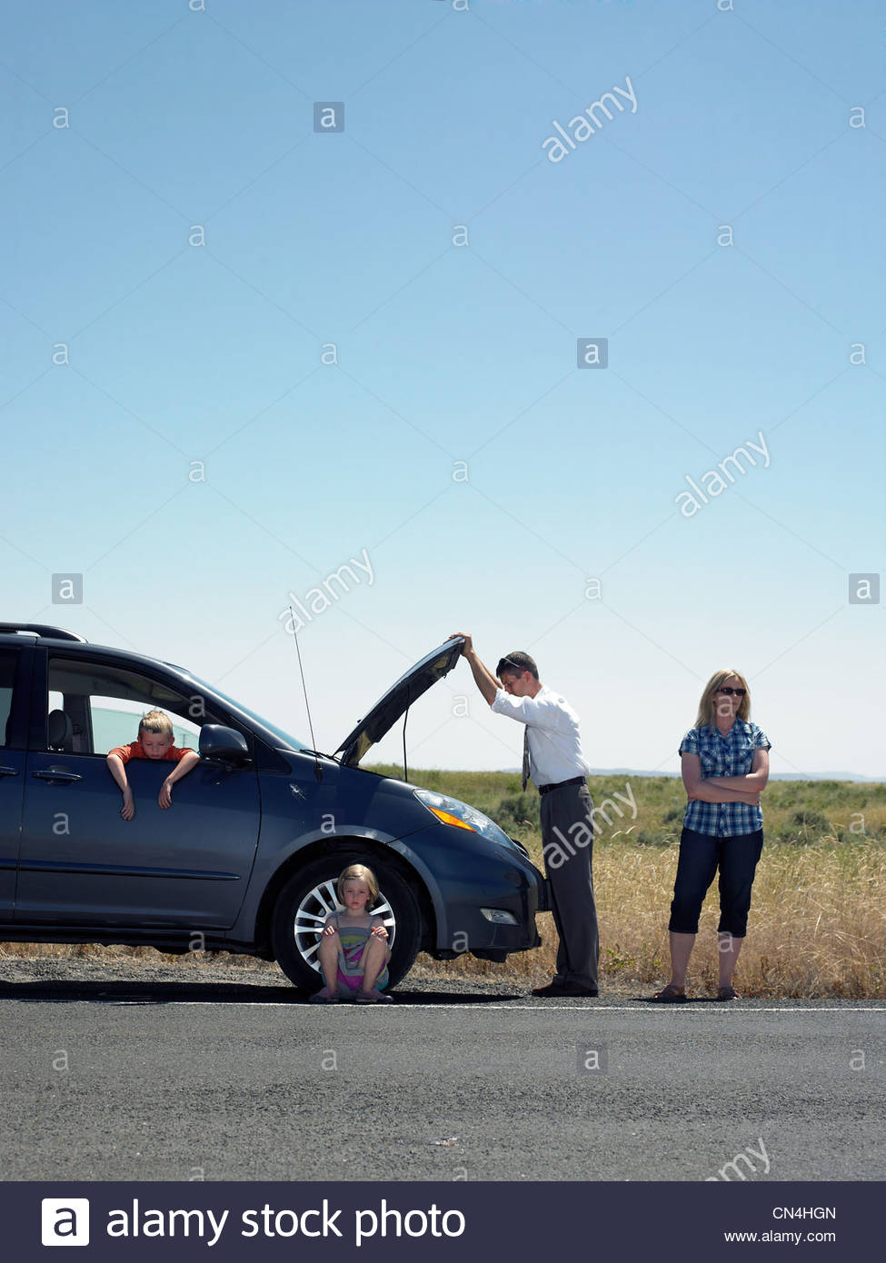 Parents and children at roadside with broken down car - Stock Image