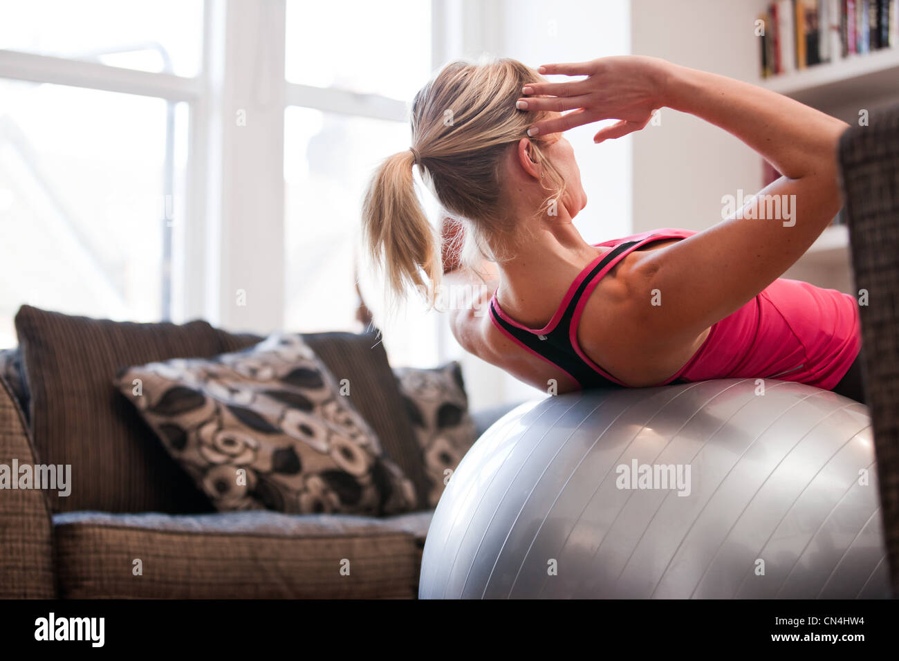 Mid adult woman performing sit ups on exercise ball at home - Stock Image