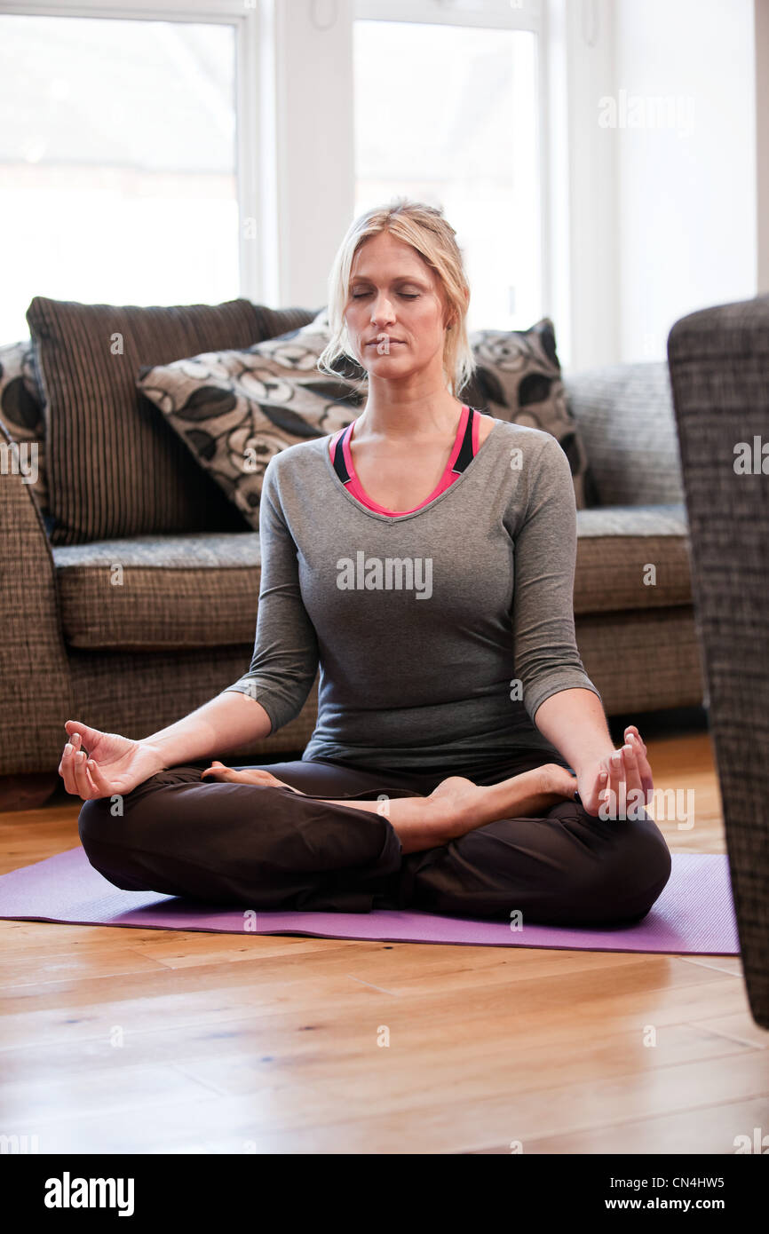 Mid adult woman in yoga pose at home - Stock Image