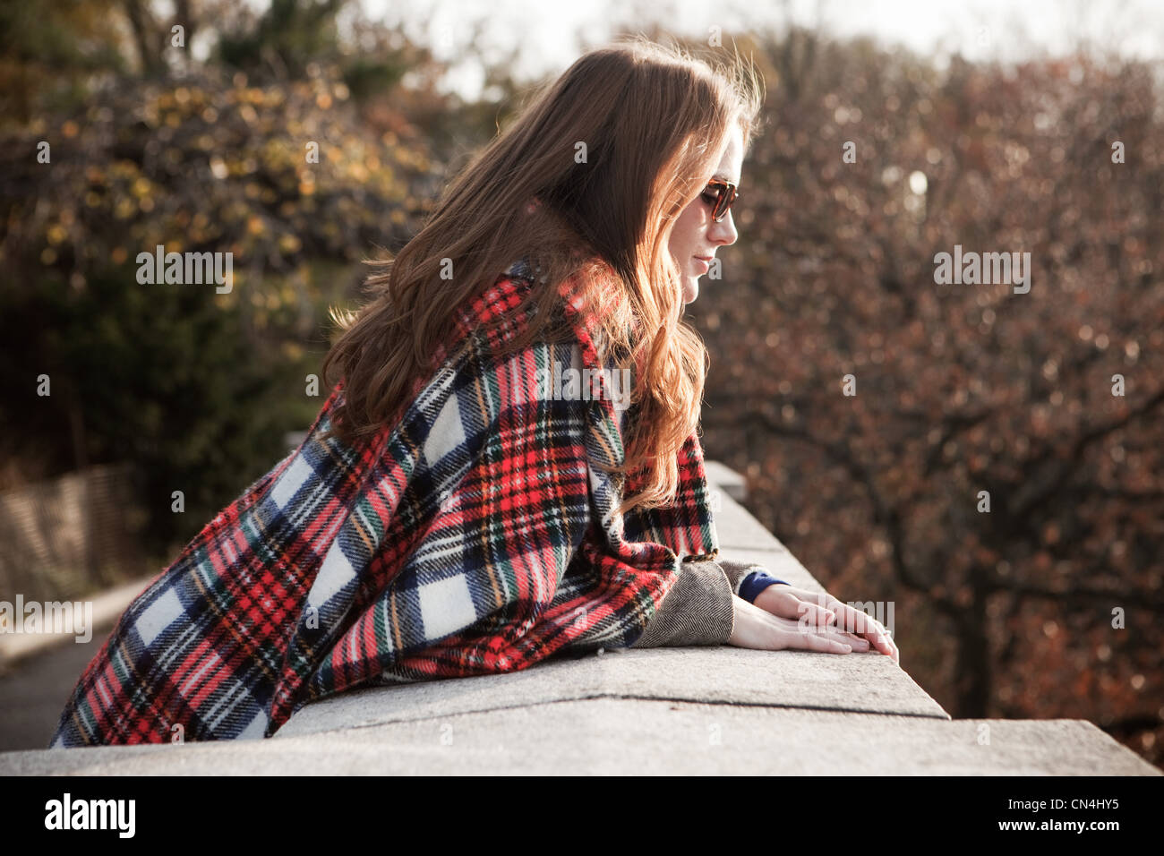 Girl with plaid blanket looking over wall - Stock Image