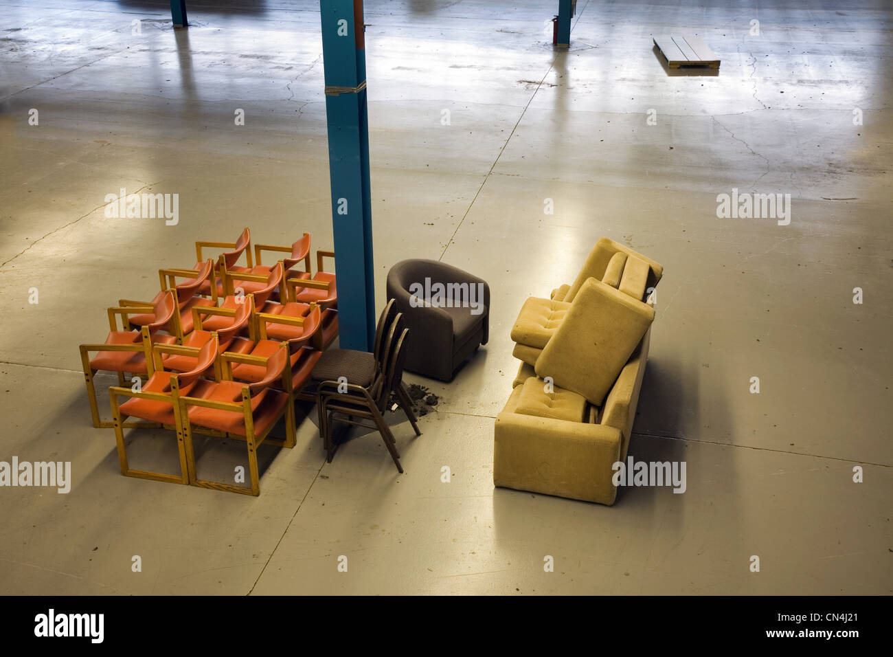Chairs stacked in an empty warehouse - Stock Image