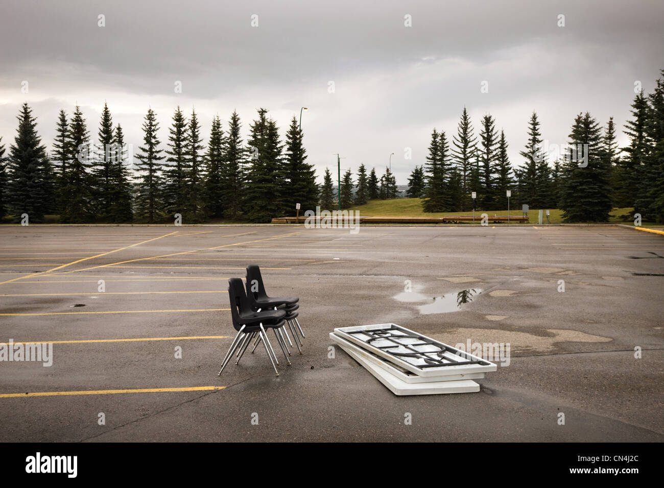 Chairs and tables left in a parking lot Stock Photo