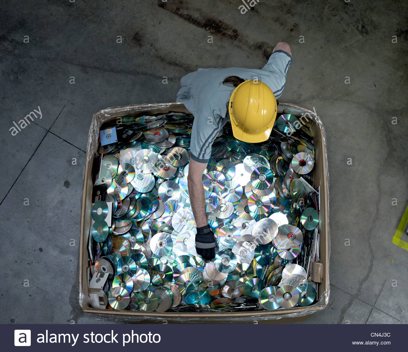 Worker sorting through discs in recycling warehouse - Stock Image