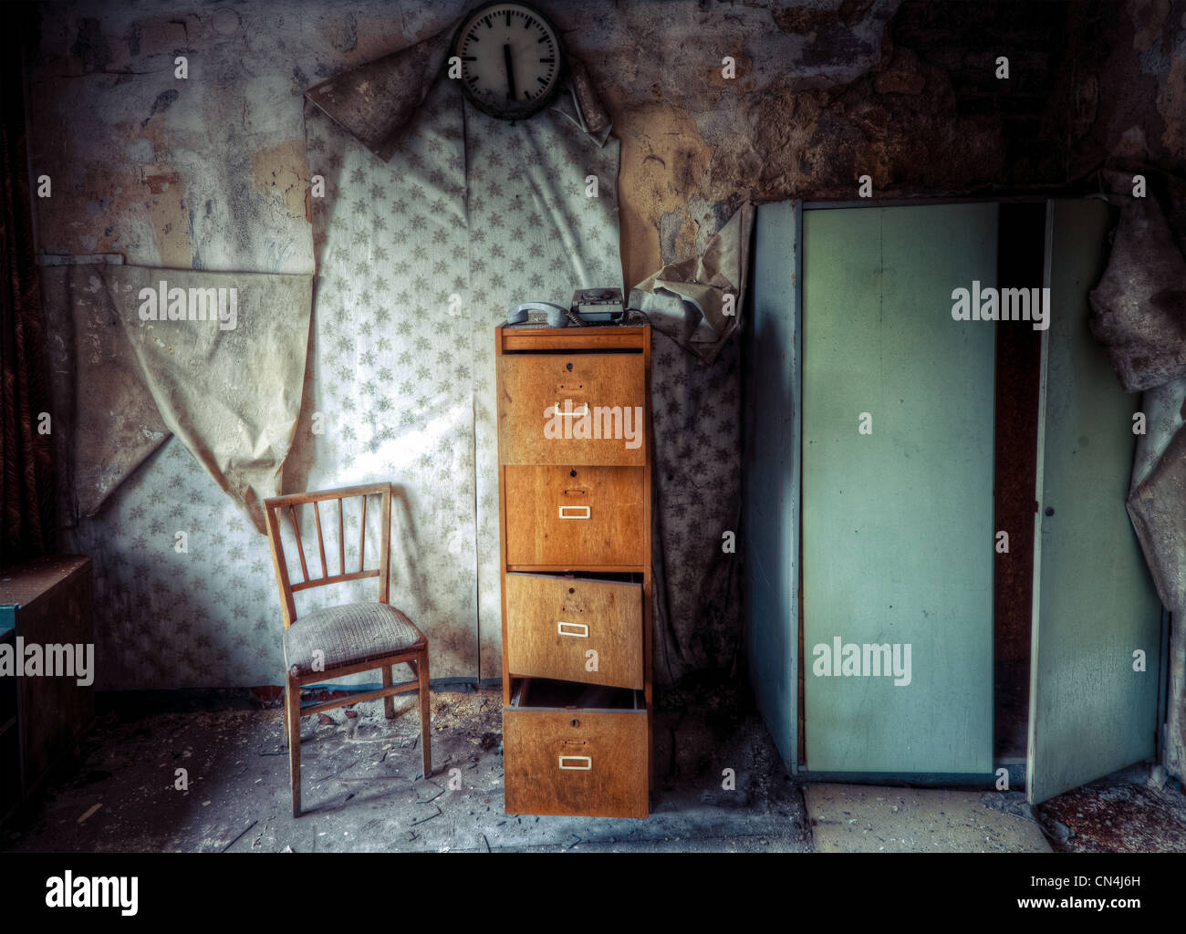 Abandoned building with chair and filing cabinet - Stock Image