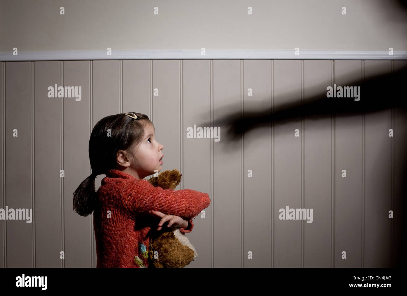 Frightened little girl and shadow of adult hand pointing at her - Stock Image