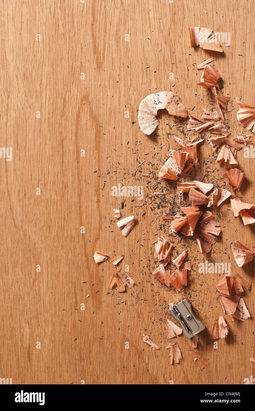 Sharpener and pencil shavings on wooden background - Stock Image