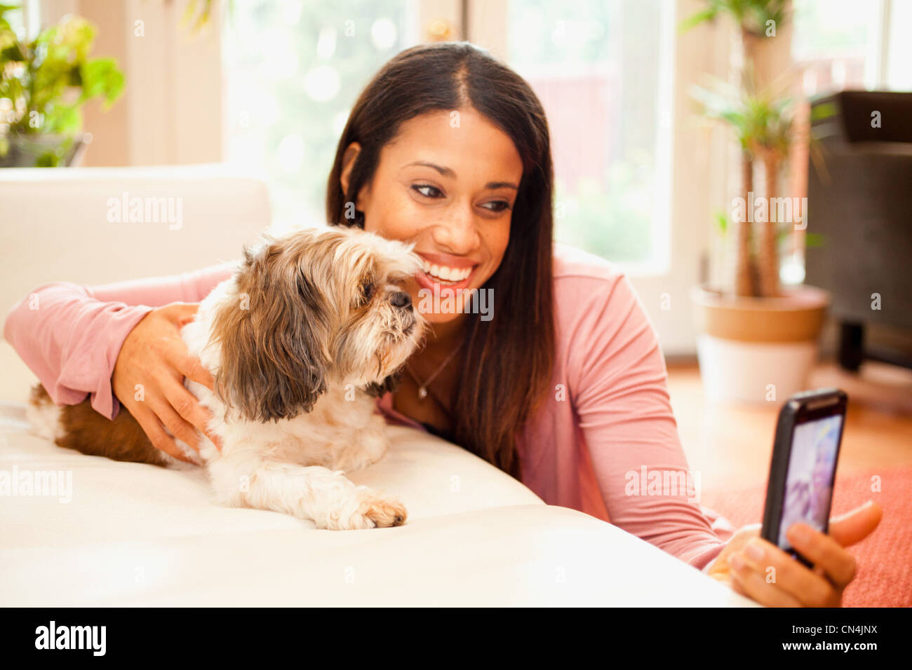 Woman taking picture of herself and her pet dog on smartphone - Stock Image