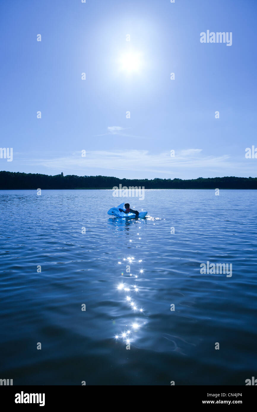 Boy swimming in lake with an inflatable dolphin, Brandenburg, Germany - Stock Image