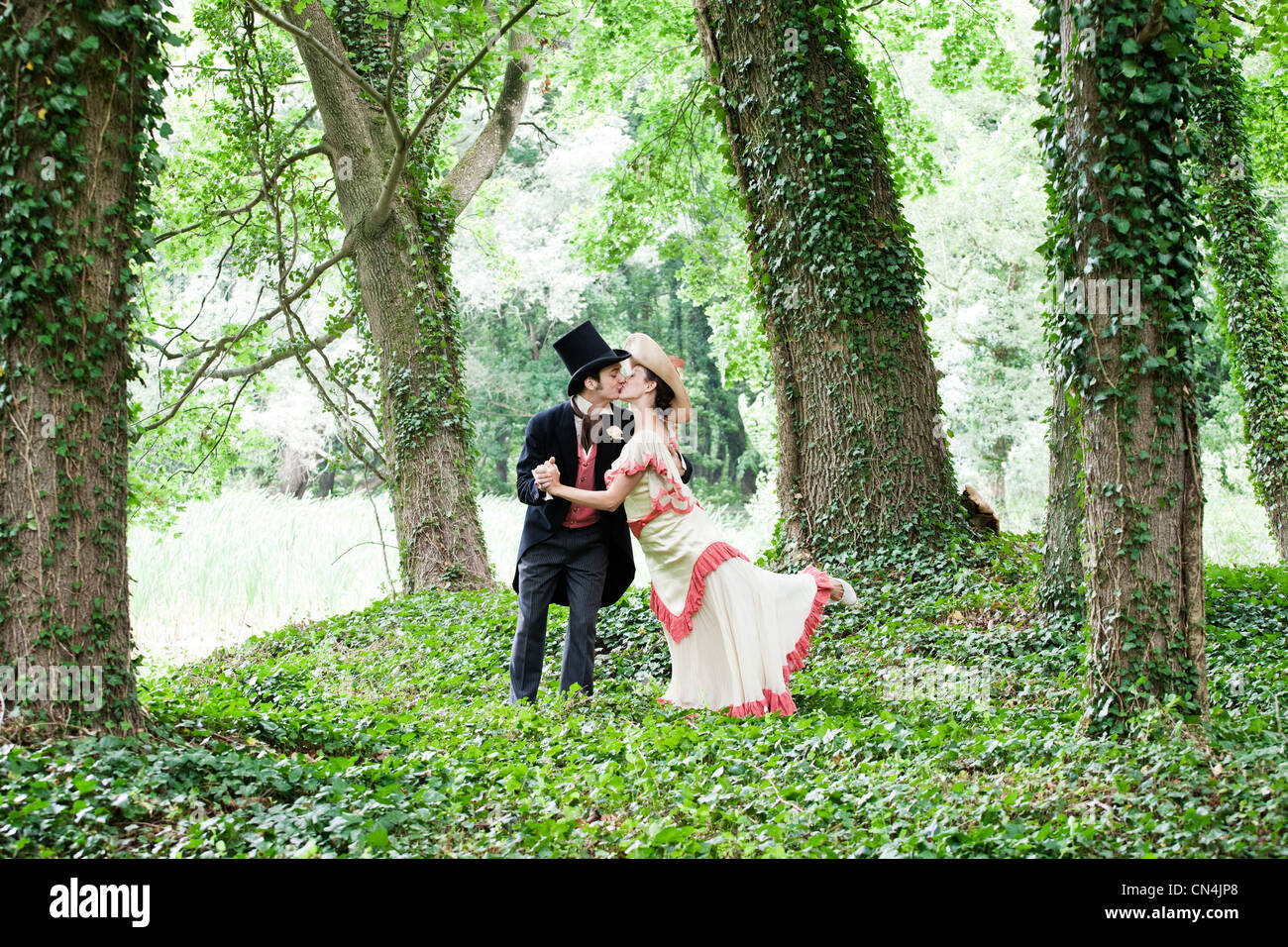 Bridal couple in 1920s style clothing, kissing in park - Stock Image