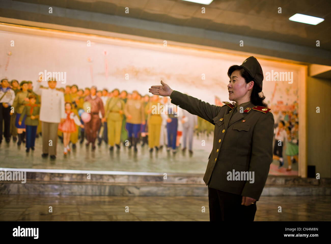 North Korea, Pyongyang, Victorious Fatherland Liberation war Museum, female soldier guide describing a frescoe showing - Stock Image