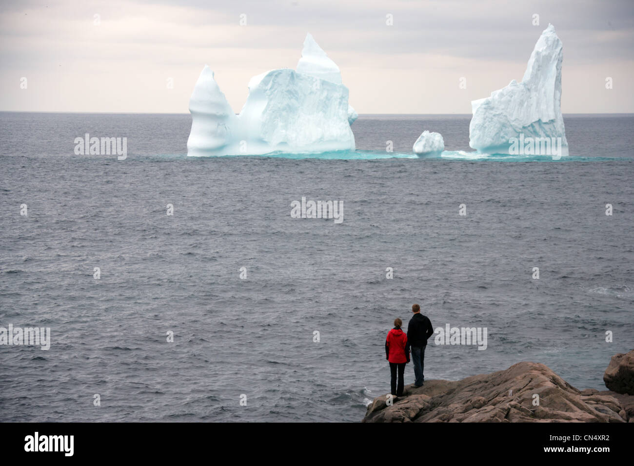 Couple looking out at an Iceberg, Cape Spear, St. Johns, Newfoundland - Stock Image