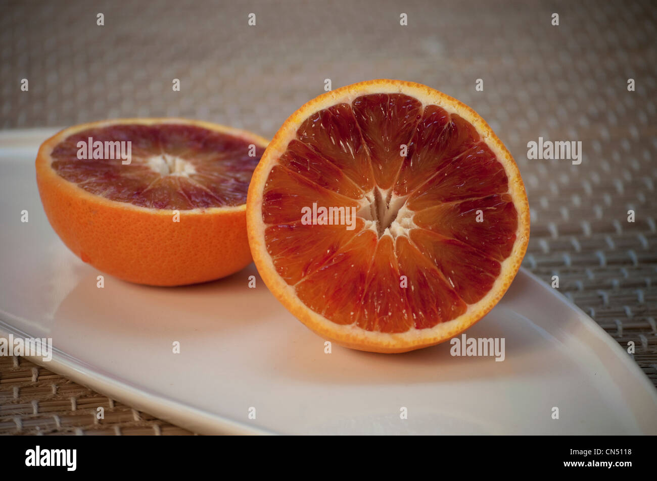 bright red blood orange on a cream coloured plate stock photo