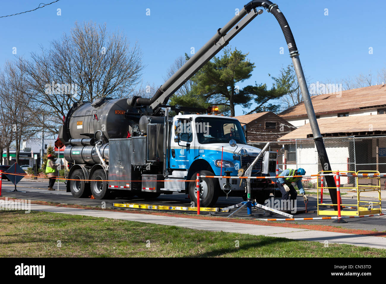 A Con Edison vacuum truck crew works on a street in White Plains, New York. - Stock Image