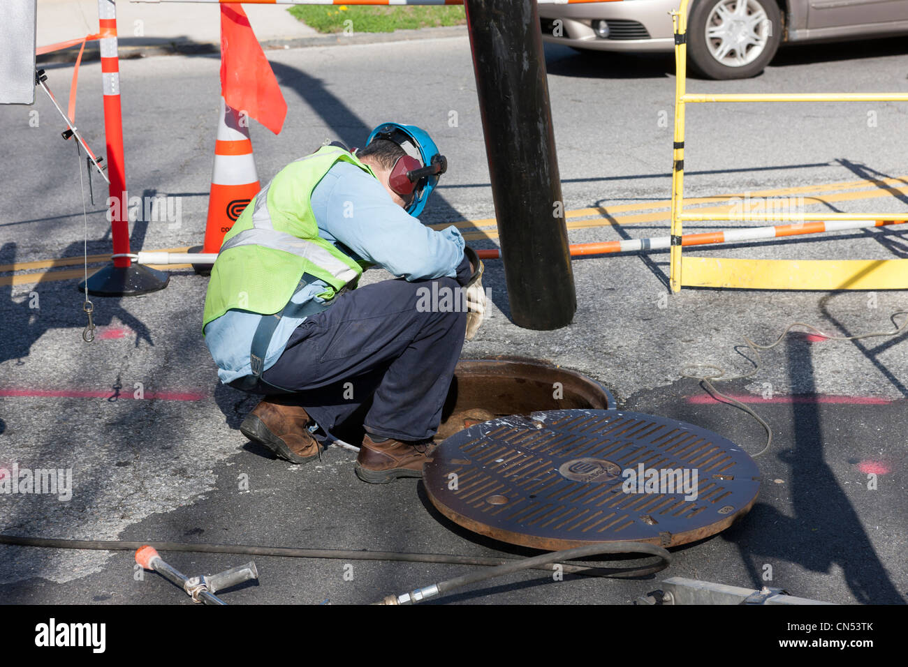 A Con Edison crew member works by a manhole on a street in White Plains, New York. - Stock Image