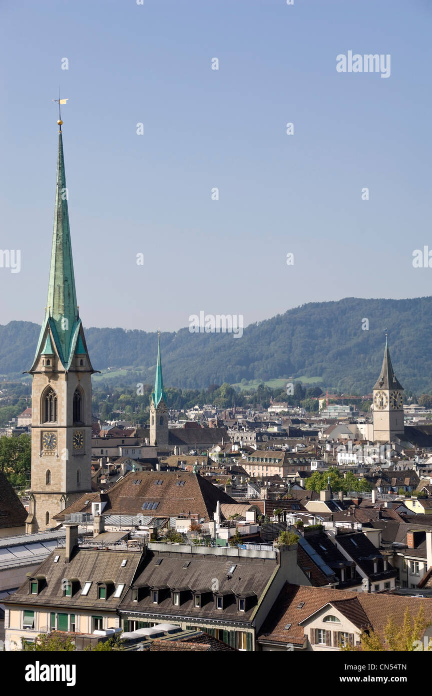Vertical view across Zurich's skyline with Predigerkirche, Fraumünster kirche and St Peter kirche spires - Stock Image