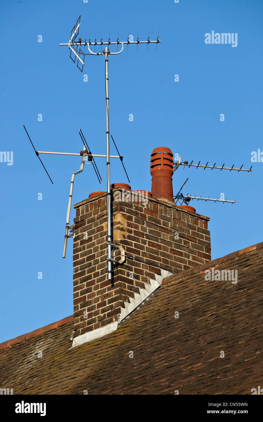 TV aerials on a brick chimney stack on the roof of a house, London, England, UK - Stock Image