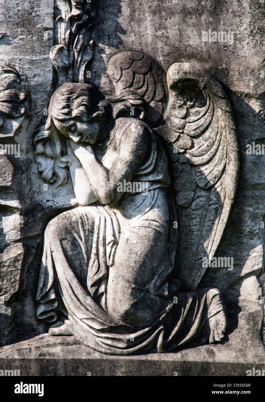 Carving of a sleeping angel on an old tombstone. - Stock Image