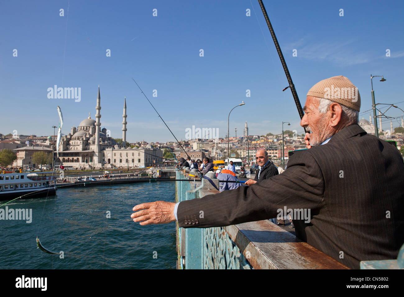 Turkey, Istanbul, fisherman on the Galata bridge spanning the straits of the Golden Horn, in the background the - Stock Image