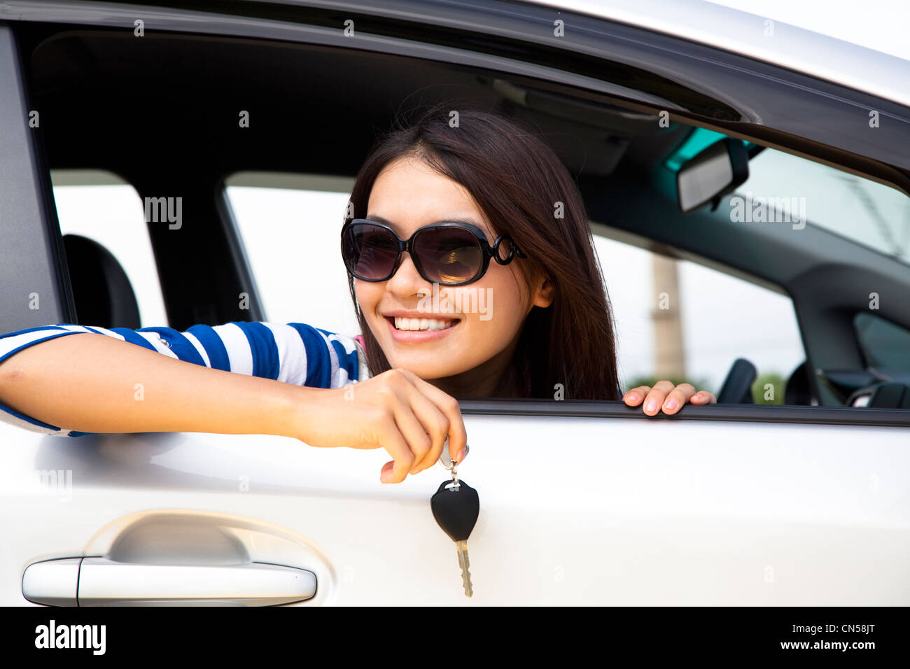 young woman holding key in car - Stock Image
