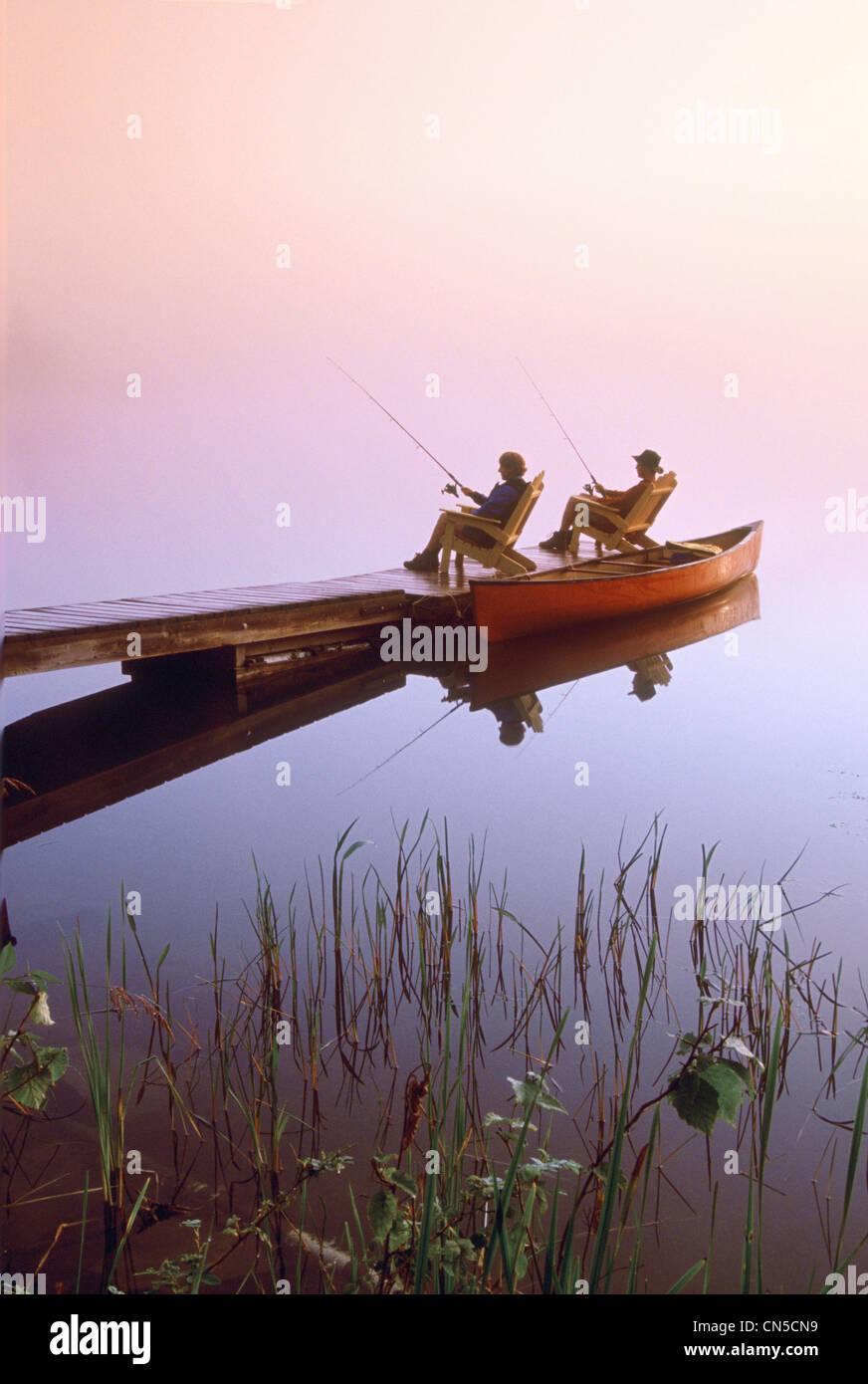 Couple Fishing off Dock, Winnipeg River, Pinawa, Manitoba Stock Photo