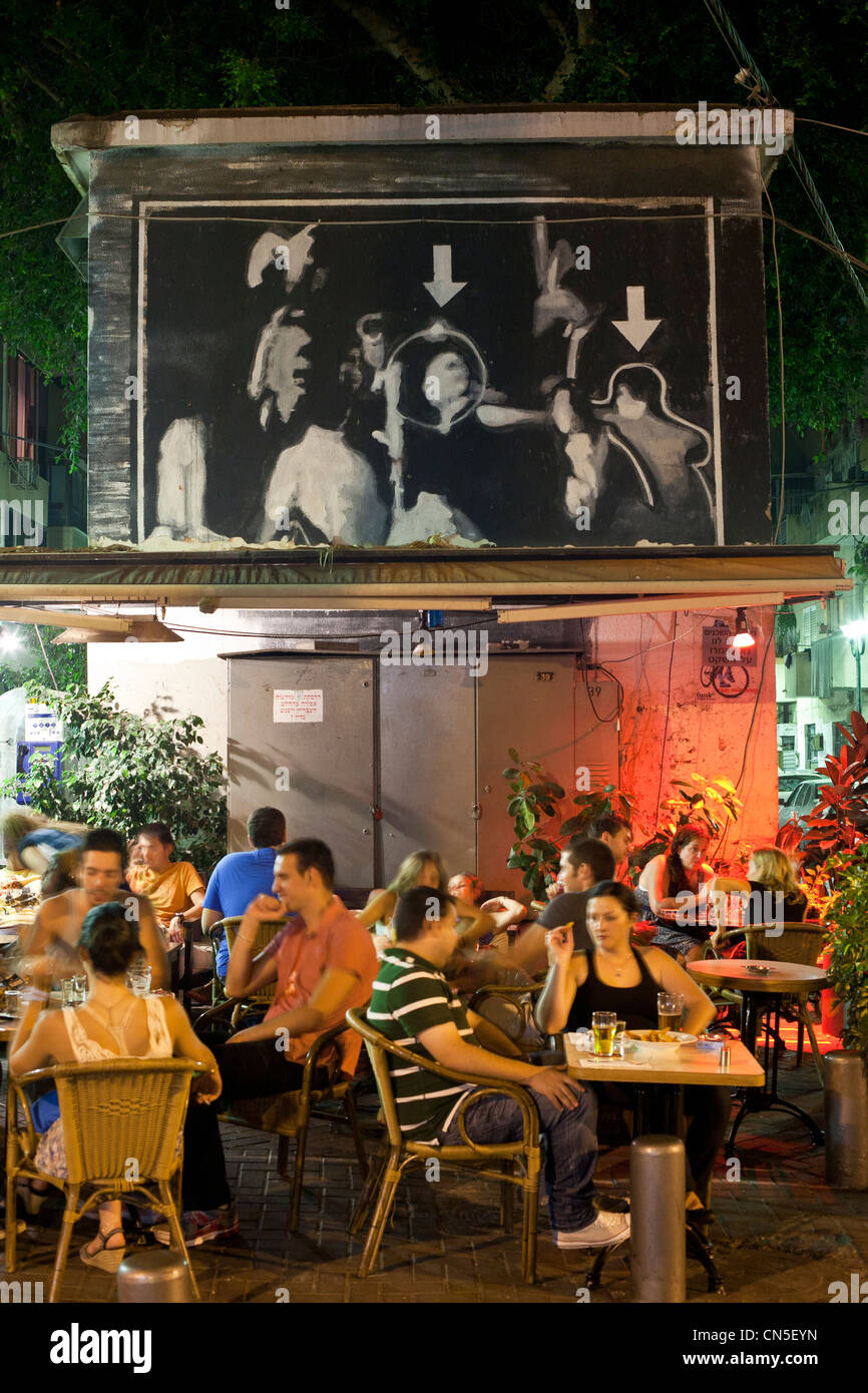Israel, Tel Aviv, Florentin district, Florentine Street, bar restaurant Bugsy, patio with mural illustrating assassination - Stock Image