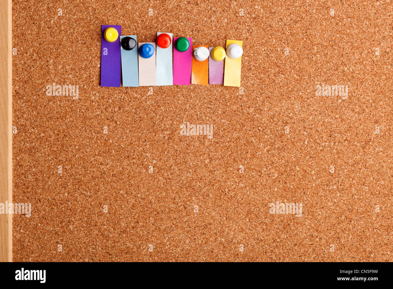 Cork board and colorful heading with copyspace for an eight letter word - Stock Image