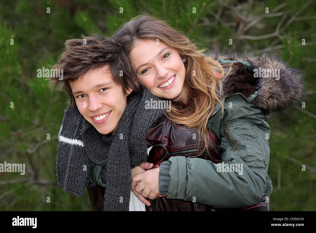happy smiling teen couple in piggy back in winter clothing - Stock Image