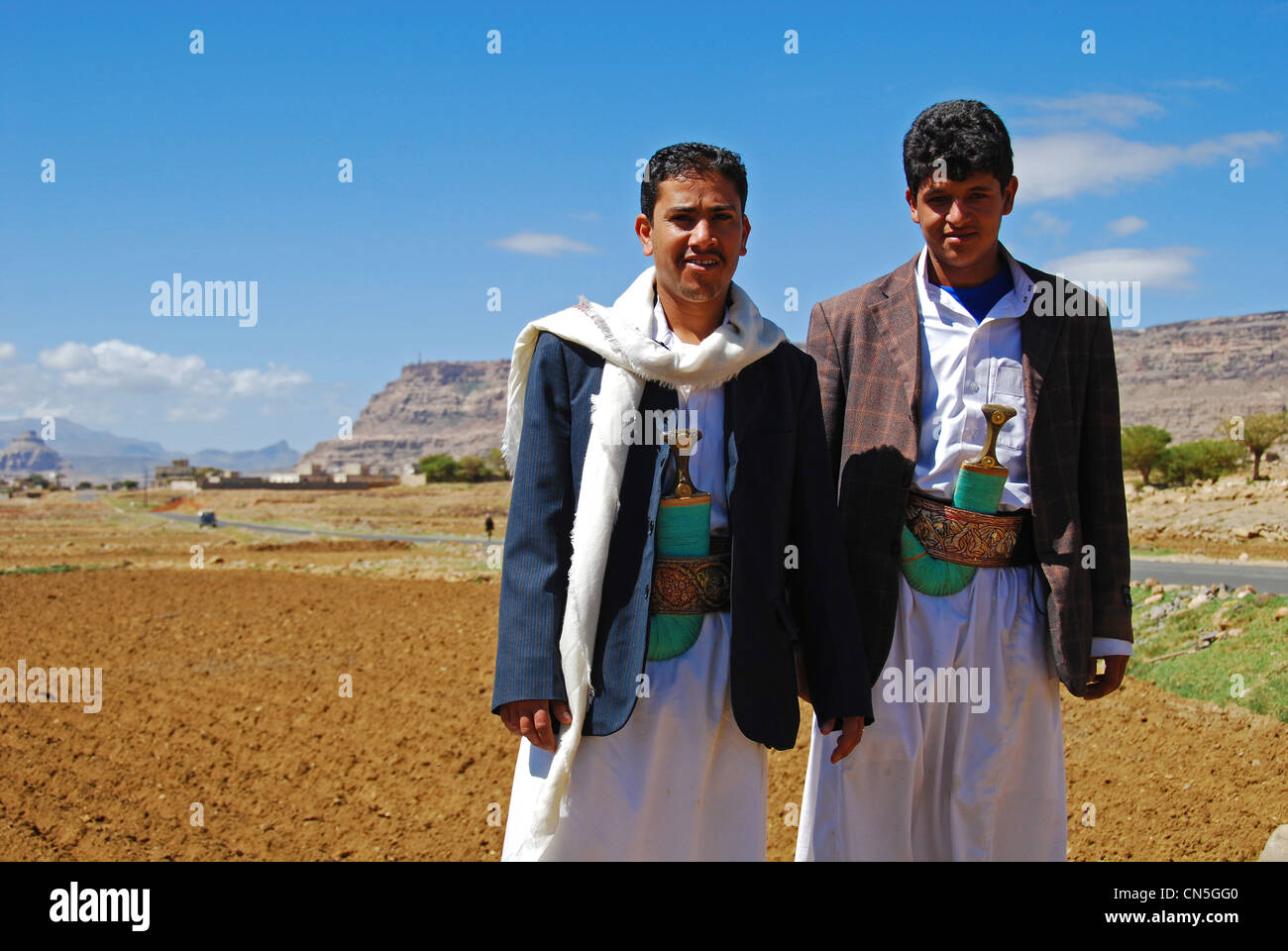 Yemen, Inland, portrait of smiling local men standing with famers ploughing field in the background - Stock Image