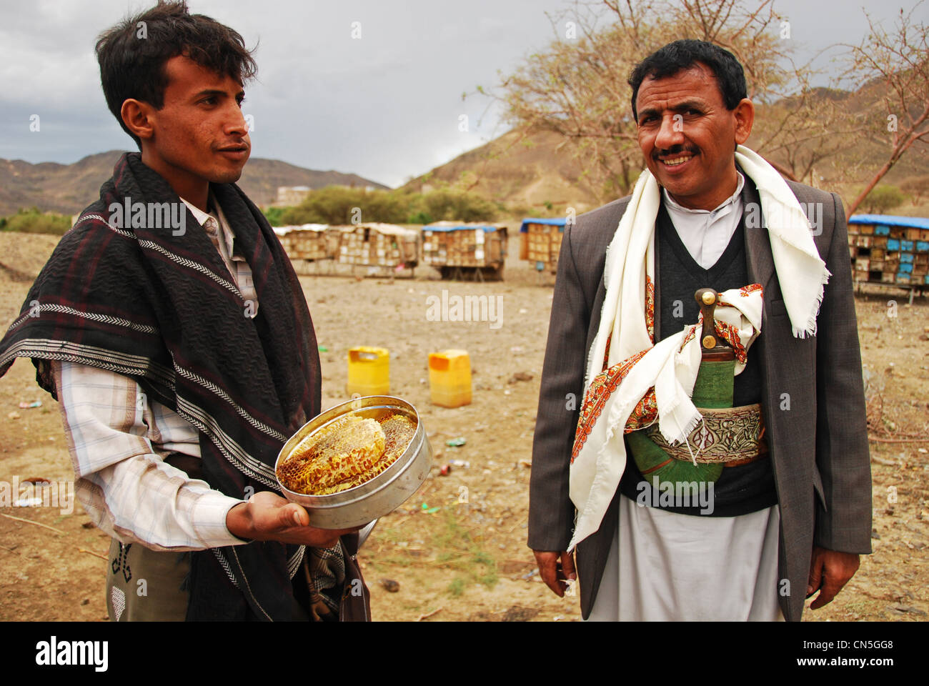 Yemen, Inland, traditional dressed man looking honeycomb seller with beehives locker in the background - Stock Image