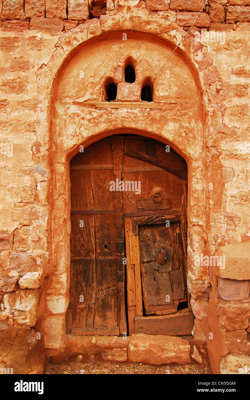 Yemen, Highlands Region, Sanaa Governorate, Kawkaban, view of a built structure with rustic wooden door at arched - Stock Image