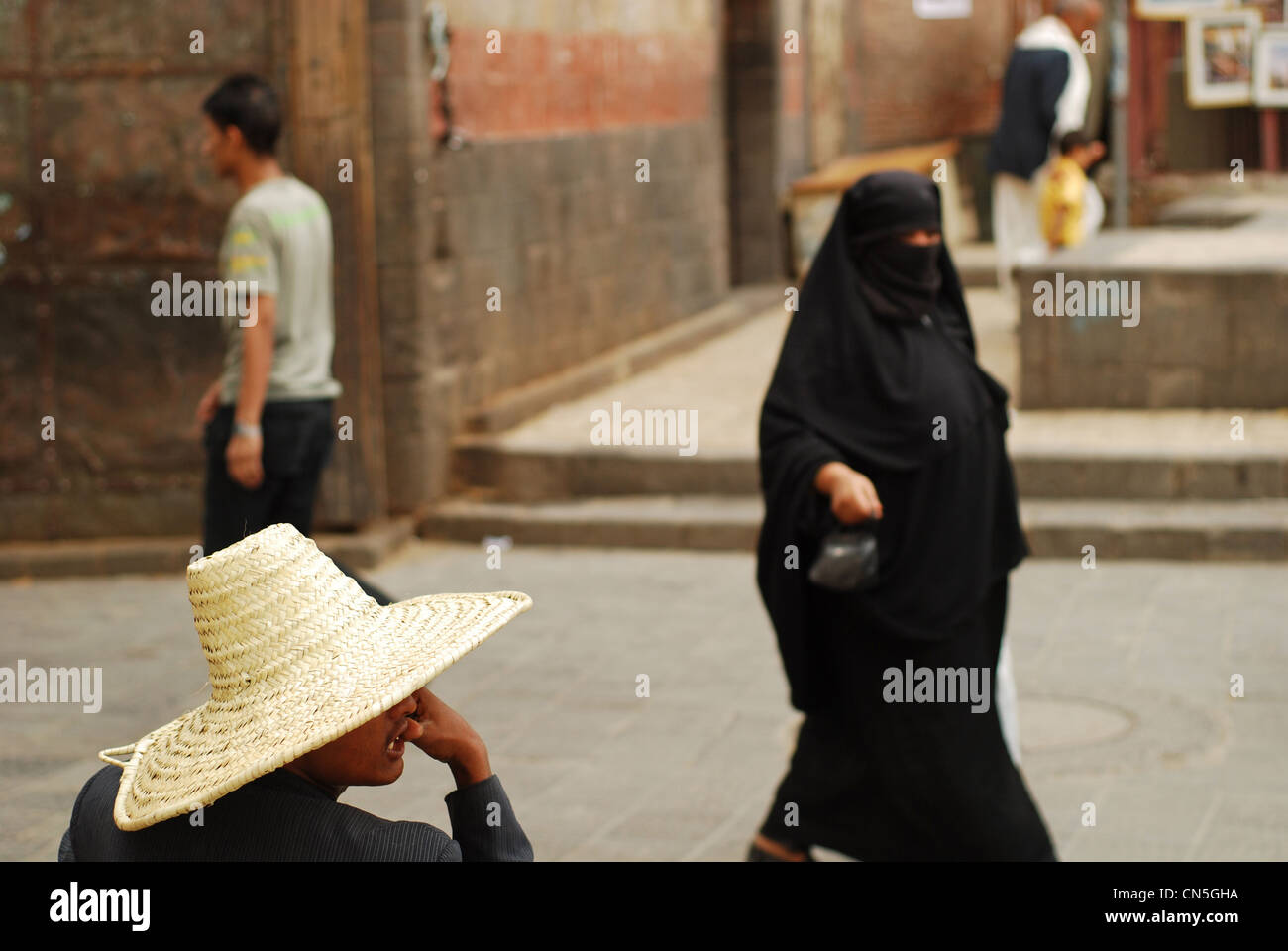 Yemen, Sanaa, view of a person wearing hat while others walking - Stock Image