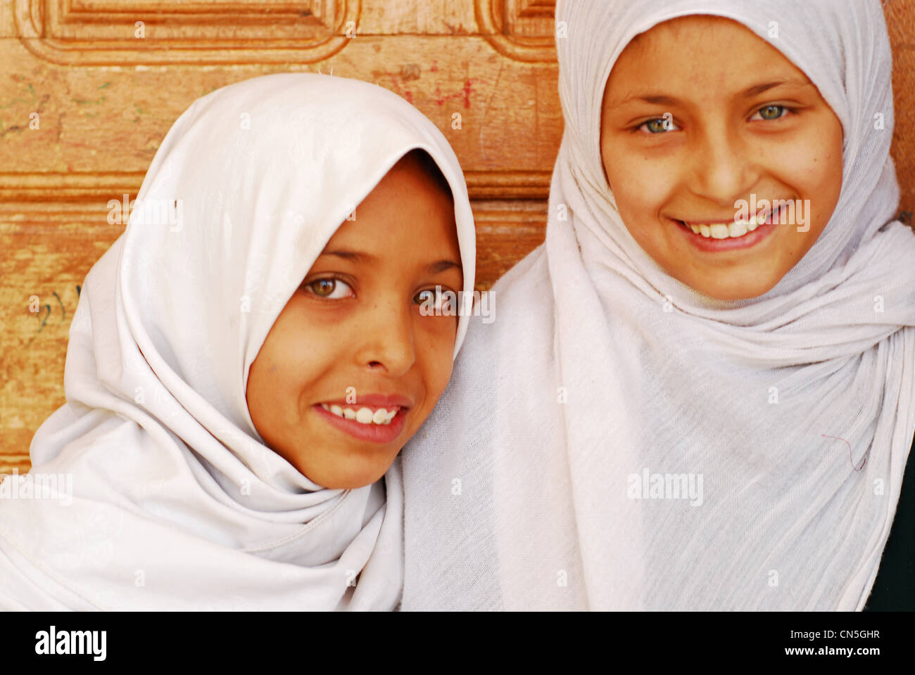 Yemen, Sanaa Governorate, Sanhan, close-up portrait of girls wearing headscarves standing together by door and smiling - Stock Image