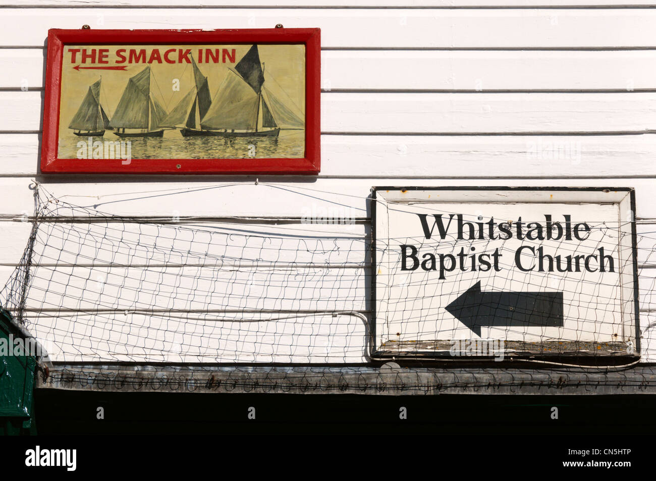 Signs for The Smack Inn and Baptist Church on a building in Whitstable High Street, Kent. - Stock Image