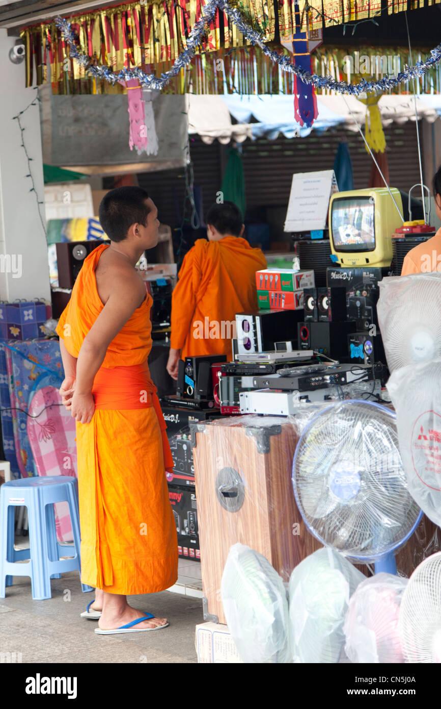 Monks in an electrical goods shop in Chiang Rai (Thailand). Moines dans un magasin d'électroménager à Chiang Rai Stock Photo