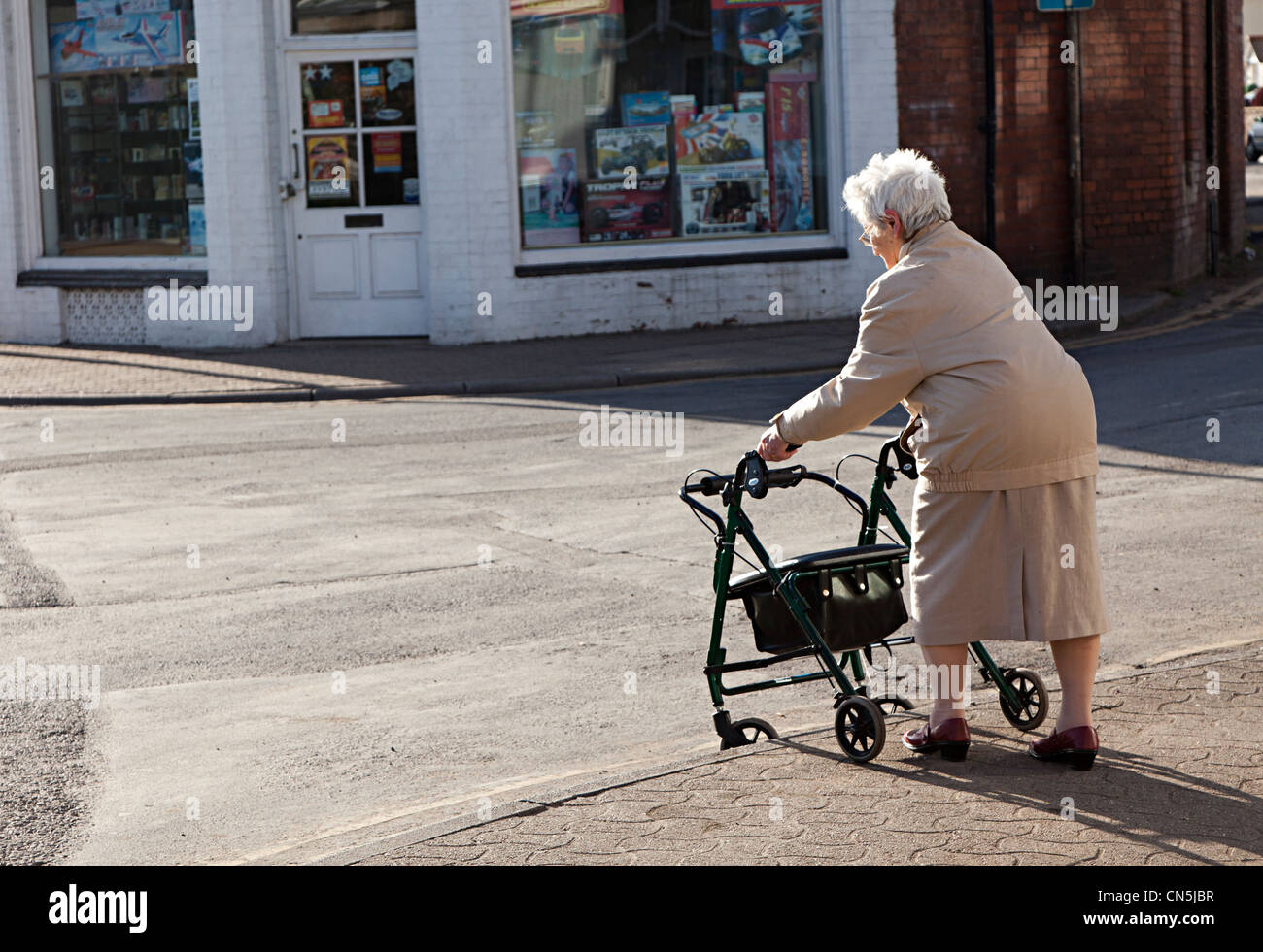 Old woman pushing shopping chair down kerb in street, Abergavenny, Wales, UK - Stock Image