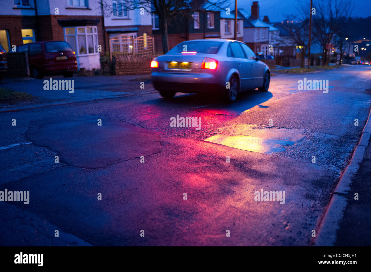Potholes and patching in the road - Stock Image