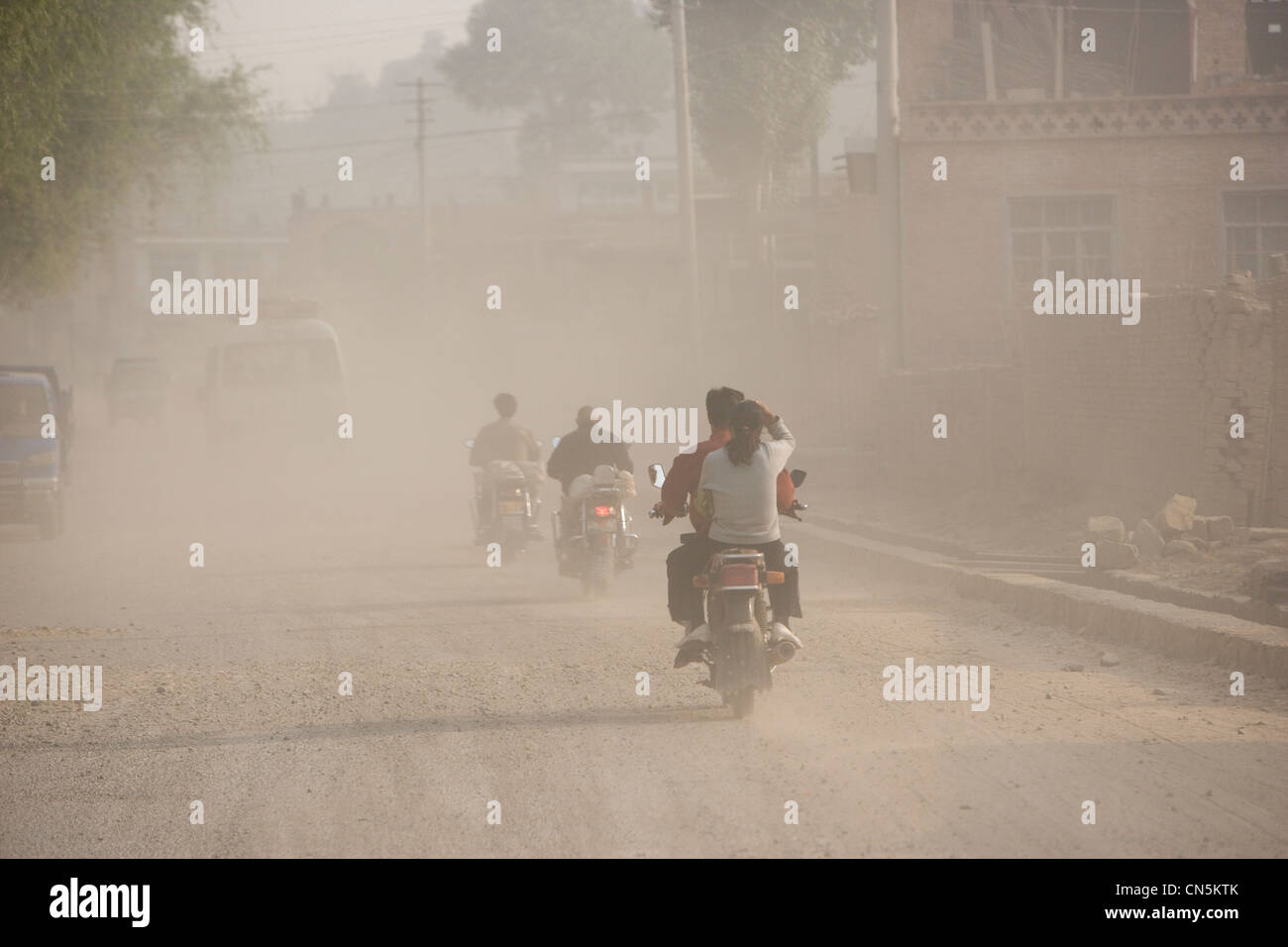 LINXIAN, HENAN PROVINCE, CHINA - JUNE 2006: Vehicle traffic throws up dust on a road under repair. - Stock Image