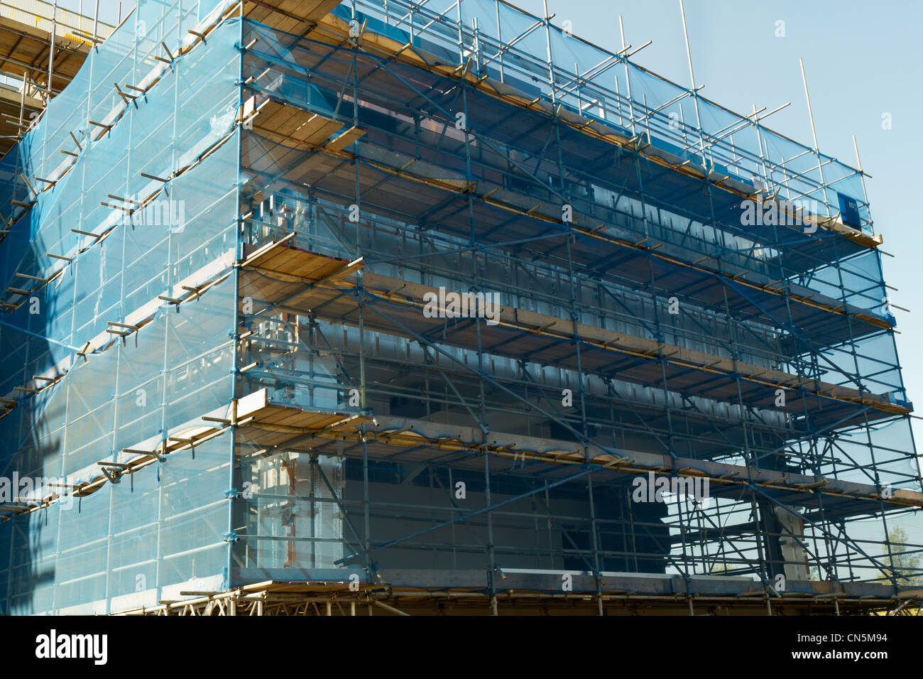 Scaffolding with protective netting on a construction site building - Stock Image