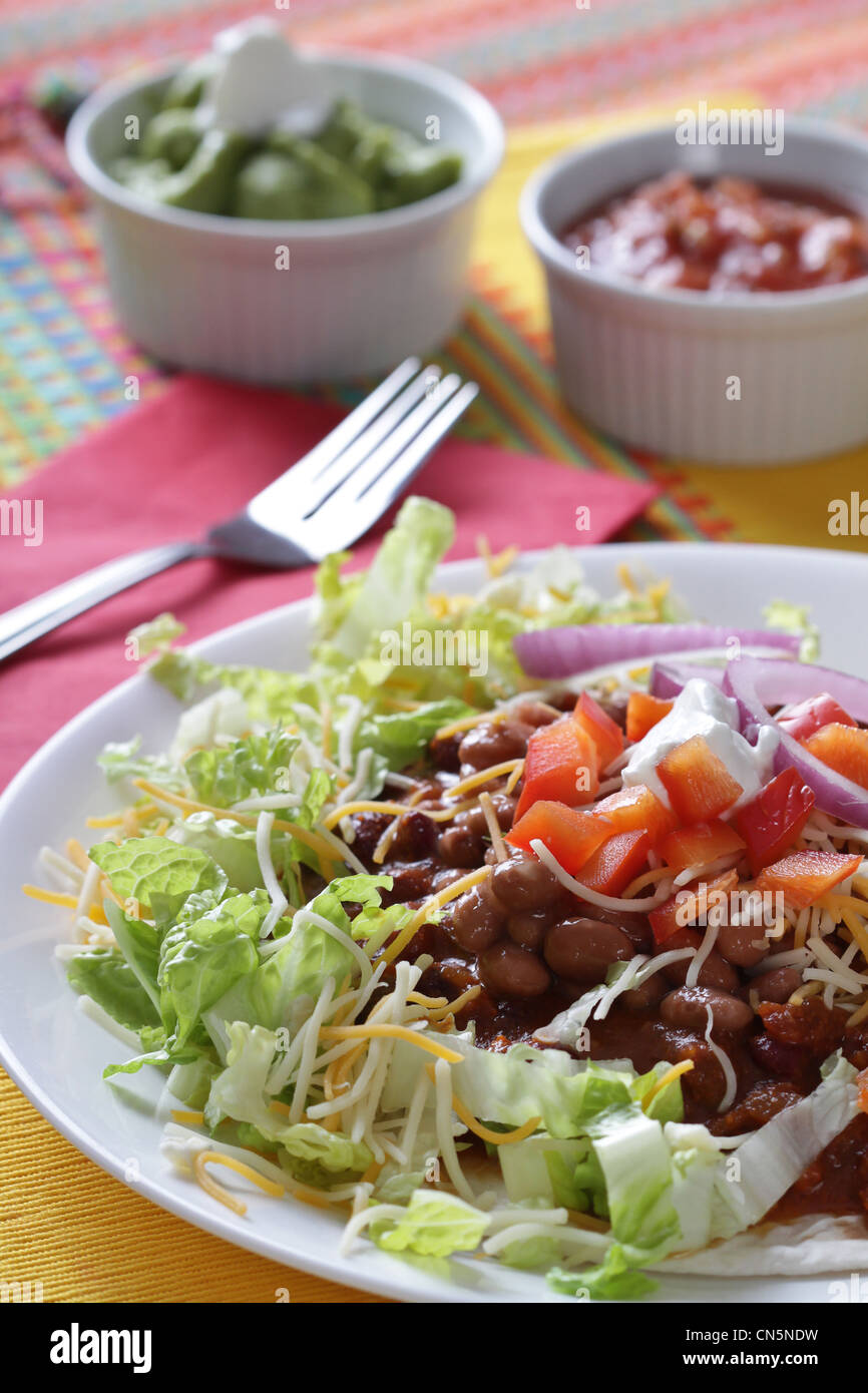 A chili bean tostada with tomatoes and sour cream on a bed of crisp lettuce with & Colorful Mexican Table Setting Restaurant Stock Photos u0026 Colorful ...