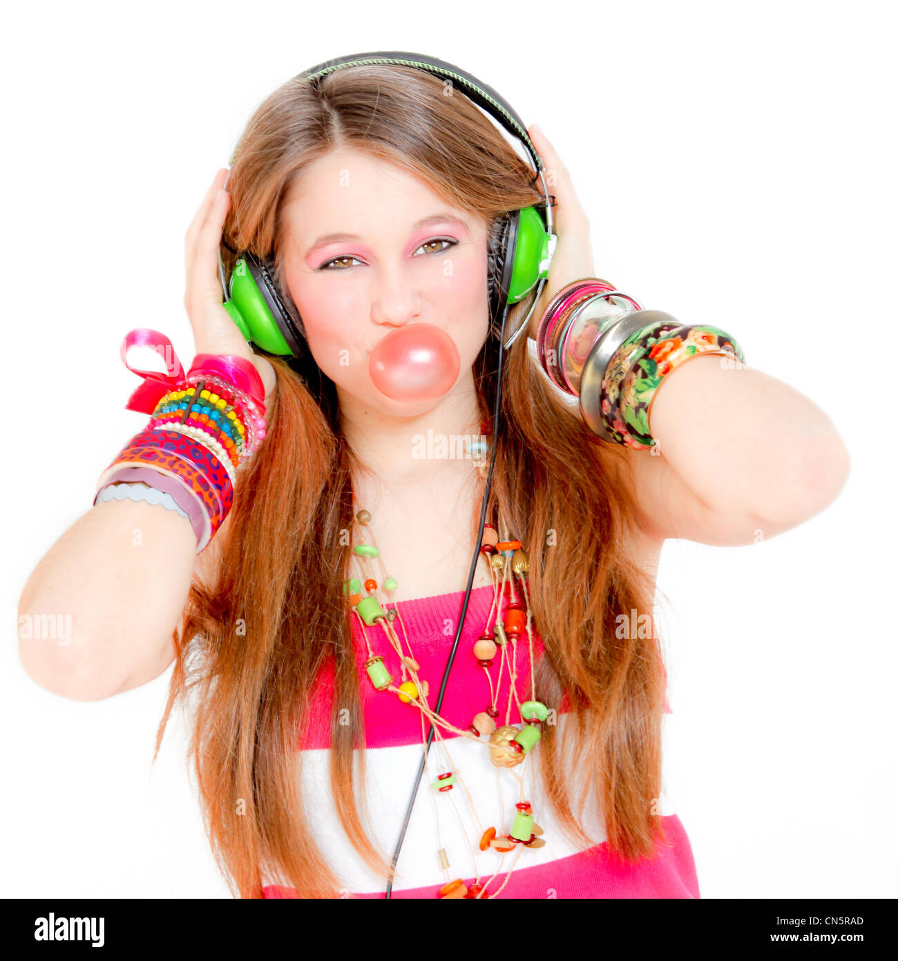 young teen girl listening to music on headphones and blowing gum - Stock Image