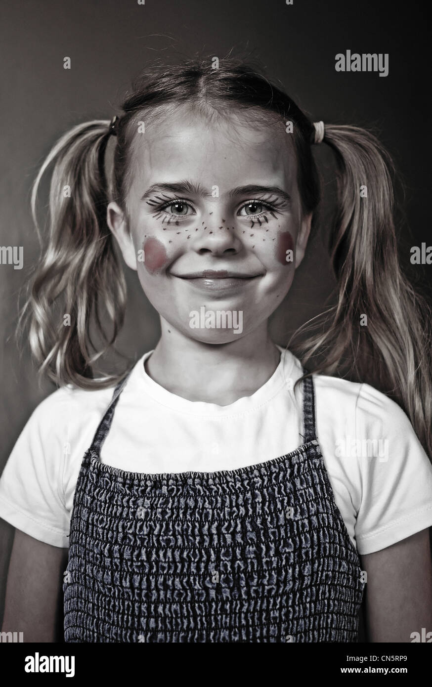 Six year old girl dressed and made up as a doll - Stock Image