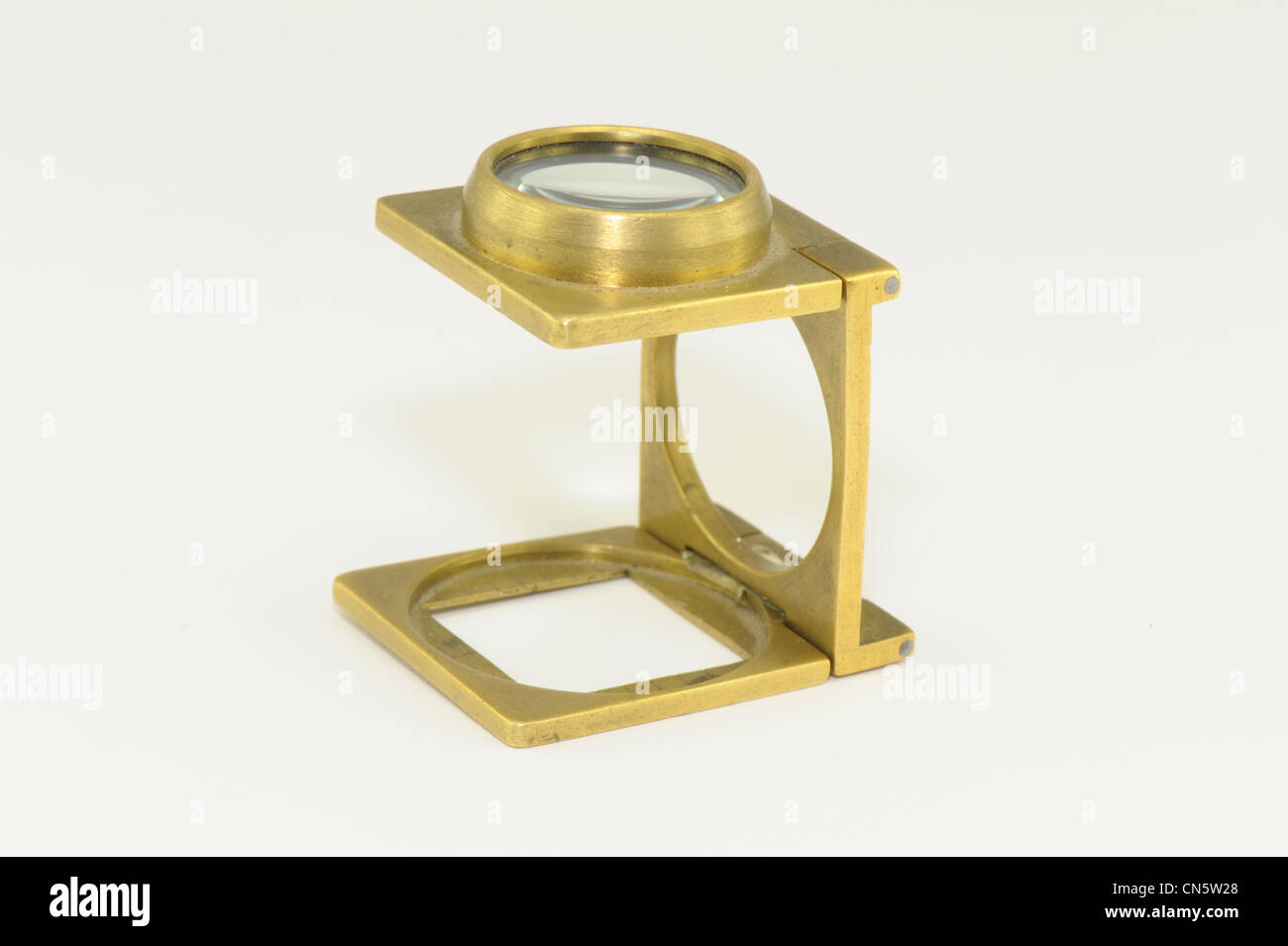 magnifying glass brass taken on a white background linen tester old fashioned - Stock Image