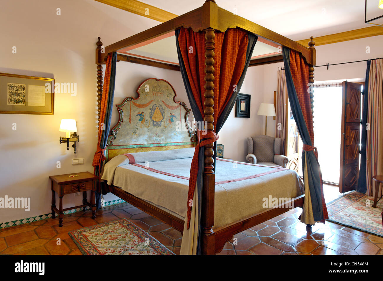 Spain, Extremadura, Guadalupe, Parador of Tourism, canopy bed in a bedroom - Stock Image